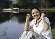 Beautiful asian woman listening music in headphones Stock Photography