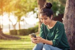 Beautiful asian woman listening music Stock Photo