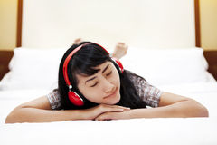 Beautiful Asian woman listens to a music on bed Stock Image