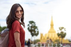 Beautiful Asian woman long hair wearing sunglasses walking on street with blurred image of Pha That Luang, Vientiane, royalty free stock images