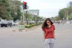 Beautiful Asian woman with long hair wearing sunglasses walking on street royalty free stock image
