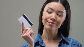 Beautiful Asian woman looking on credit card and thinking about spending money. Stock footage stock footage