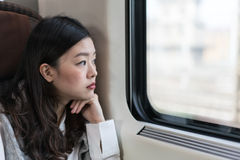 Beautiful asian woman looking out of train window, with copy space Royalty Free Stock Image