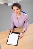 Beautiful Asian woman looks up from work desk Royalty Free Stock Images