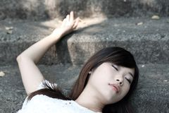 Beautiful Asian woman lying down with her eyes closed. By herself stock image
