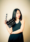 Beautiful asian woman with movie clapper board vintage colors ef. Beautiful asian woman showing movie clapper board, seductive look and vintage colors effect Royalty Free Stock Photography