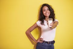 Beautiful asian woman offering a glass of fresh milk. Portrait of beautiful asian woman offering a glass of fresh milk on yellow background Royalty Free Stock Photography