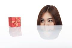 Beautiful Asian woman peeking look at red gift box Royalty Free Stock Image