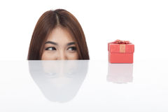 Beautiful Asian woman peeking look at red gift box Stock Photo