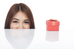 Beautiful Asian woman peeking with red gift box. Isolated on white background Royalty Free Stock Image