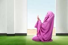 Beautiful asian woman in pink veil sitting in praying position and raise the hands on the carpet inside the room stock images