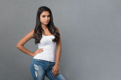 Beautiful Asian woman in plain white tank top and blue jeans. Posing with arm akimbo on light gray background stock image