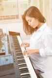 Beautiful asian woman playing piano Stock Photos