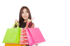 Beautiful Asian woman point to empty space with shopping bags Stock Images
