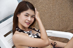 Beautiful Asian woman on poolside chair. Stock Photography