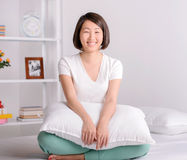 Beautiful asian woman. Portrait of Asian female sitting on bed at home Stock Photos