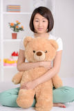 Beautiful asian woman. Portrait of Asian female sitting on bed and hugging soft toy at home Stock Photography