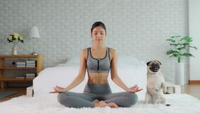 Beautiful Asian woman practice yoga lotus pose with dog pug breed enjoy and relax with yoga in bedroom at home