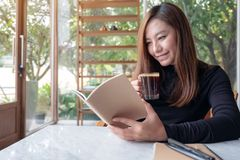 A beautiful asian woman reading a book while drinking coffee in cafe royalty free stock photography