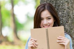 Beautiful Asian woman reading book in the park. On holiday self-learning royalty free stock images