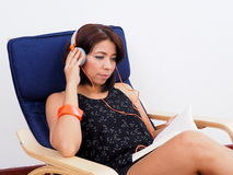 Beautiful Asian woman reads book and listens to music Royalty Free Stock Photo