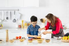 Beautiful Asian woman in red shirt and black apron teaching her stock photography