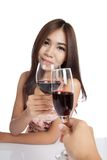 Beautiful Asian woman with  red wine cheers to another guy Stock Image