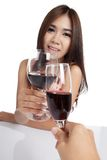 Beautiful Asian woman with  red wine cheers to another guy Royalty Free Stock Images