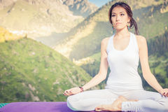 Beautiful asian woman relaxing and meditating outdoor at mountain Royalty Free Stock Image