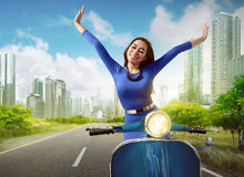 Beautiful asian woman riding a scooter Royalty Free Stock Images