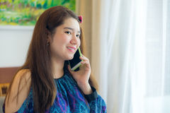 Beautiful Asian woman in a room is using her mobile phone to com Stock Photos