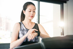 Beautiful asian woman running treadmill. smartwatch check pulse. Beautiful asian woman running treadmill use smartwatch check pulse rate. indoors gym background Stock Photography