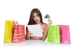 Beautiful Asian woman shock with a credit card statement and shopping bags. Isolated on white background stock photo