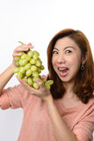 Beautiful asian woman shocked expression while holding grape Royalty Free Stock Photography