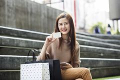 Beautiful asian woman with shopping bags and a card Stock Photography