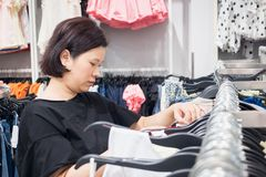 Asian woman shopping in fashion clothes store Stock Images