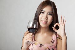 Beautiful Asian woman show OK sign hold glass of  red wine Stock Image