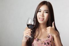 Beautiful Asian woman show thumbs up hold glass of red wine Royalty Free Stock Images