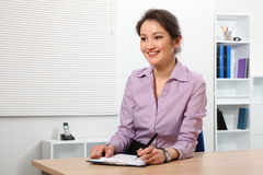 Beautiful Asian woman signing document at work Royalty Free Stock Image