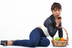Beautiful Asian woman sits next to a fruit basket Stock Photography