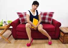 Beautiful Asian woman sits with notebook on red sofa Stock Images