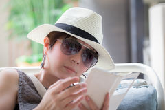 Beautiful asian woman sitting on the chair and reading SMS Royalty Free Stock Photo
