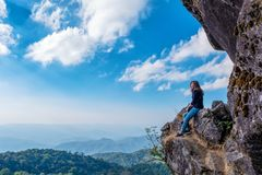 A beautiful asian woman sitting on a cliff with mountains view royalty free stock image