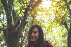 A beautiful Asian woman sitting at outdoor with feeling happy in green nature background. Closeup portrait image of a beautiful Asian woman sitting at outdoor Royalty Free Stock Photos