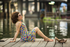 Beautiful asian woman sitting on a wooden embankment of the river. Walking. Royalty Free Stock Photos