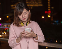 Beautiful Asian woman with smart phone and yellow headphones Stock Photos