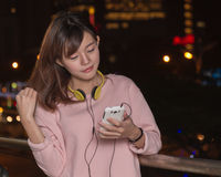 Beautiful Asian woman with smart phone and yellow headphones Stock Photography