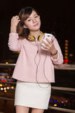 Beautiful Asian woman with smart phone and yellow headphones Royalty Free Stock Image