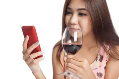 Beautiful Asian woman smile with cellphone and red wine Stock Photo