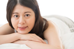 Beautiful asian woman smile face to camera, lie on bed Royalty Free Stock Photo